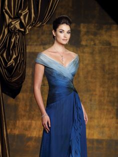 Stunning shades: Mother of the Bride or Mother of the Groom Gown/Bridesmaid Gown - Style No. 112949  »  Montage by Mon Cheri -   Description   ›  Off-the-shoulder crinkle ombre silk chiffon A-line dress with V-neckline, ruched crisscross bodice with asymmetrical waistline, skirt features side cascading ruffled sash and sweep train.  Sizes: 4 – 20, 16W – 26W. Colors   › Blue
