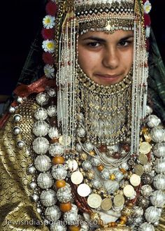 Photograph of a Yemenite Jewish girl, , Irit Kapach, wearing golden ceremonial dress and gold and silver jewelry. Goldsmiths and other craft people are among the Jews who emigrated to Israel from Yemen. Yemenite Jewish brides in a traditional wedding ceremony may wear this golden dress. The rings and necklaces are made of gold, silver, and jewels. Photograph by Nathan Benn taken November 1, 1979 in Jerusalem, Israel.