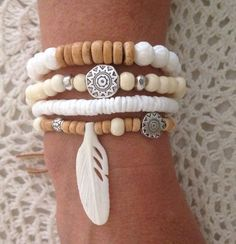 this listing is for 4 bracelets  White bohemian stack  1. Coconut beads, bone beads, silver Tibetan beads, bone feather 2. Off white bone beads and silver Tibetan beads threaded onto sturdy jewellery elastic. Natural faux suede tie. 3. White carved lotus shell, natural coconut beads 4. White shell beads  delivered to you in an organza bag.