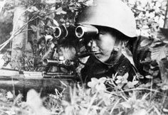 Sergeant P. Dorzhiev, Was a legend in Russia during As a sniper he killed 181 Germans on the Leningrad front, here he is looking through binoculars searching out the enemy closely holding his rifle, taken sometime in