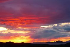 Fiery June sunset over the Inner Hebrides, Scotland, with rain shower in the distance over the Isle of Canna. [Photo by Jenny Chapman.]