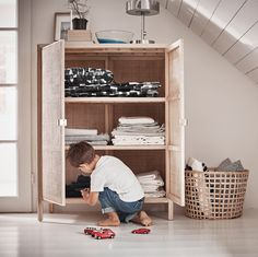 A boy sitting on the floor playing with cars in front of a rattan cabinet with the doors open.