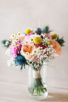Well, this has some fun elements! I do love the little daisies in it. That was my mom's favorite flower. I love the spiky blue things and the yellow pom poms. I love the texture of the peachy flowers. I would want burgundy to be in this somewhere. - Amanda