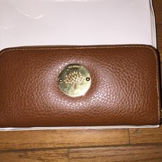 Vintage brown leather Mulberry wallet Vintage brown leather mulberry Wallet with gold logo medallion on front plus zipper pull. Wallet has 12 interior credit card slots and one zippered compartment. Mulberry Bags Wallets