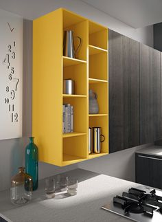 Playing the part of an elegant social kitchen, Snaidero CODE makes the transition between the living area and the kitchen organic and pleasant, thanks to the wide array of modular units and classy cupboards and open shelves. Details of open unit cupboard in Curry Yellow Matte lacquer #SnaideroUSA | Michele Marcon Design