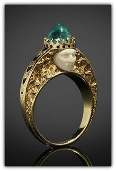 RENÉ LALIQUE | A finger ring by René Lalique in yellow gold, each side centred by a carved ivory face, the ring is surmounted by a cabochon emerald, the setting of the stone formed and enamelled to resemble a crown, the subject's hair sensuously tumbles down the deeply engraved shoulders, the top of the shoulders are decorated with overlapping engraved leaves filled with black enamel.