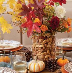 Herbstblätter in einer Glasvase mit Nüssen gefüllt