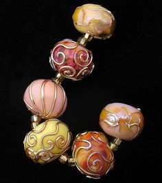 The silvered stringer lines and spirals on these beads are delightful!
