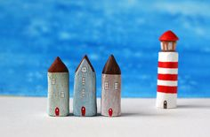 Three little clay houses and a striped lighthouse - light green, brown, blue, red and white