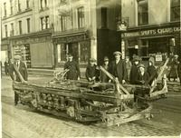 Patrick Street, Cork, Monday morning after burning -- A number of civilians (and a tram driver?) looking at the remains of a burned out tram. The caption reads 'Patrick Street, Cork, Monday morning after burning' (by Auxiliaries and Black and Tans on 11 December 1920?). Premises in background include James Mangan Ltd, Tivoli Restaurant and a tobacconist's shop. One little boy is smiling broadly at the camera.image