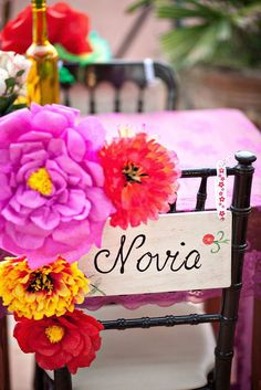 Mexican-themed wedding, Frida Khalo inspired wedding. Flowers on back of chair.