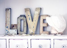 """""""Love"""" letters with vintage photos, bonnet display on thread roll."""
