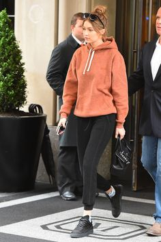 Hadid stepped out in off-duty athleisure, pairing a muted orange sweatshirt by Kith NYC with black joggers and sneakers, plus a Versace bag and Karen Walker sunnies.