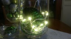 Bead garlands in a hurricane jar with a string of lights, and a sequin pinecone for good luck ;)
