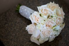 Handtied of cream roses, white spray roses, white calla lilies, stephanotis accented with rhinestones throughout the bouquet, finished with a rhinestone wrap around the stems.