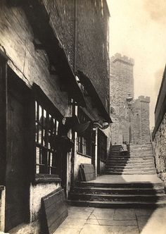 : A view of Castle Stairs Newcastle upon Tyne taken in 1924. The view is looking up Castle Stairs towards the Castle Keep. On the left-hand side are two shops with the wooden shutters propped up against the front wall. The proprietor of one of the shops is 'J.D. Detchon'.