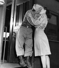 A military couple kiss goodbye at Camp Patrick Henry in August 1945 as he gets on a train for a new placement.