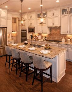 Kitchen with white cabinets, pendent lights and large island; The Colton floor plan, Drees Homes, Nashville