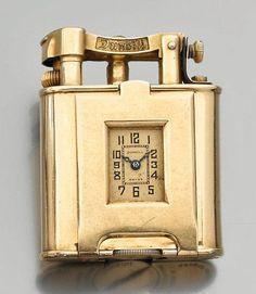 DUNHILL Rare et beau briquet en or à essence incrusté d'une montre. Boîtier carré, cadran de la montre rectangulaire avec chiffres arabes peints et chemin de fer pour les minutes. Mouvement mécanique signé… - Drouot Estimations - 18/04/2012