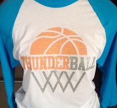 Be LOUD, Be PROUD OKC. Rock your Thunder spirit in this fun tee. Made with orange and silver glitter, this 3/4 tee is perfect for any Thunder lovin