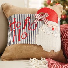 """Embroidered """"ho ho ho"""" pillow wrap features layered burlap Santa with contrasting bow on traditional ticking background. Secures with Velcro at back."""
