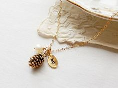 A adorabe necklace inspired by mother nature. This piece features a dainty pinecone adorn with a freshwater pearl your and hand stamped leaf charm with the letter of your choice. { HOW TO ORDER } 1. Select options for Letter Initial and Freshwater Pearl from the pull-down menu. After