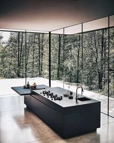 Minimal black kitchen island bench surrounded by tall windows with natural light Modern home House design