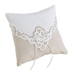 "A tan cotton pillow with ivory lace overlay and satin bow becomes a charming accent for the wedding ceremony. It measures 7.75""."
