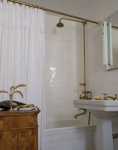 Brass exposed shower tub plumbing fixture and matching sink faucet with subway tile.