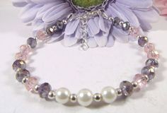 Elegant bracelet adorned with Swarovski Purple and Pink Crystals. Bracelet accented made with Swarovski pearls and accented with silver plated round beads. Bracelet is Silver Plated with a lobster clasp.