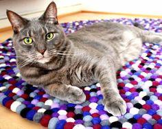 Tapis de boules Manna multicolore Le Manna est fun et bien adapté aux salons et aux chambres. Mettez-le dans une pièce terne et vous verrez la différence ! En plus de magnifiques boules violettes, il comporte également du bleu roi, du rose, du blanc et du bleu. Les tapis en boules de laine sont chauds, vous allez adorer la sensation que celui-ci procure sous les pieds. #sukhi #tapis #boules #laine #multicolore #violet #chat