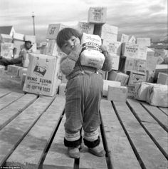 A young girl holds up a bag of sugar in Iqaluit, 1960