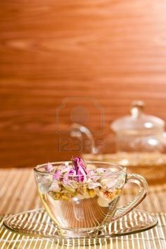 Pink rose tea in a glass teacup on bamboo mat and wood background