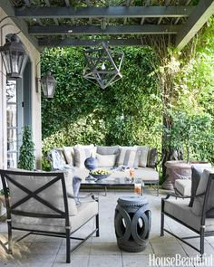 """""""The house is on a golf course with manicured lawns, so I liked repeating the grays and ivories of the interior against all the greenery,"""" designer McDonald says of the limestone-tile veranda in a Los Angeles house, which has Restoration Hardware furniture."""
