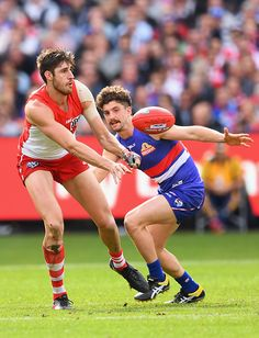 #AFLGF2016 Sam Naismith of the Swans handballs whilst being tackled by Tom Liberatore of the Bulldogs during the 2016 AFL Grand Final match between the Sydney...