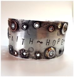 """Hand riveted cuff with """"Faith Hope Love"""" stamped on it."""