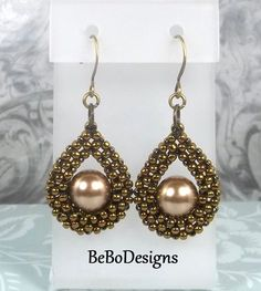 Elegant and classic teardrop earrings are made with Toho antique bronze seed beads and feature a 10mm Swarovski bronze pearl nestled in the bead work. The teardrop is hand sewn in the Cubic Right Angle Weave (CRAW) stitch with Wildfire beading thread. The ear wires are antiqued gold plated brass. These earrings measure 1 3/4 inches in overall length including the ear wires. Thank you for visiting my Etsy Shop.