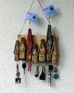 Sieben schnucklige Häuser in verschiedenen Größen zieren dieses Schlüsselbrett. Die Dächer wurden in verschiedenen Farben gestaltet. Die beiden längsten Häuser dienen auch als Notizzettelhalter....