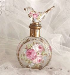 this beautiful hand-painted glass perfume bottle is an original by Debi Coules. Adorned with French roses in pinks, creams and whites, with greenery, and accented with antique gold leaf is absolutely exquisite! Placed on your vanity, side table or anywhere you would like something beautiful Each bottle is one of a kind and is certain to be the begining of your collection. Wonderfully detailed and hand painted all around the bottle so there is always something beautiful to look at.