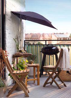 Varanda com uma mesa pequena e duas cadeiras dobráveis, tudo em acácia maciça com velatura Mostradas com um guarda-sol semicircular e um grelhador a carvão