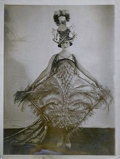 "Fall fashions at the Hotel Astor, 1920. ""The tendency for evening gown is the unique or the bizarre, and this fantasy in feathers is a gorgeous creation. The pagoda shaped hat is topped off by veri-colored ostrich plumes."" (via)"