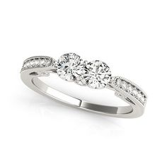 Let your love shine with this charming two-stone diamond ring. Created in 14K white gold, this ring showcases a duo of shimmering two 1/2 ct. diamonds, representing both your friendship and loving commitment, nestled side-by-side, set in precious 14K white gold setting and arranged in perfect alignment across the center of the ring. Smaller round accent diamonds are channel-set into the ring's shank, completing the design. Radiant with 1 1/5 ct. t.w. of diamonds, this exquisite two-stone…