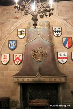 Cinderellas Royal Table - Fireplace and shields with crests in Grand Hall tami@goseemickey.com