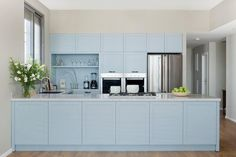 Sky blue kitchen cabinets, white marble counter top & wooden floor