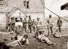 You are viewing an impressive image of Yorktown, Virginia (vicinity). Group of contrabands at Allen's farm house near Williamsburg Road.  It shows a black woman with a washboard, and another with a tub. They appear to be washing clothes. A black man is seen with an axe chopping wood. It was taken in 1862 by Gibson, James F., b. 1828.