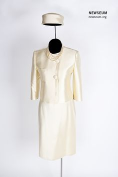 This is a designer replica of a silk suit and pillbox hat worn by Jacqueline Kennedy during a 1961 state visit to France. Oleg Cassini, the first lady's official designer, created the ensemble. The necklace is a copy of the triple-strand pearls that the first lady often wore. Photo: Sarah Mercier/Newseum; suit, hat and pearls: Loan, Oleg Cassini