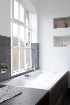 Inham boven bad, grijze tegels op de muur in combi met veel wit