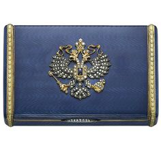 A SILVER-GILT, GOLD, DIAMOND AND GUILLOCHÉ ENAMEL CIGARETTE CASE MARKED BRITZYN, ST PETERSBURG, 1908-1917. Rectangular, enamelled in translucent blue on a wavy guilloché ground, the cover applied with a diamond-set Imperial double-headed eagle centered with a sapphire, diamond-set thumb-piece, marked inside base, 10.0 cm wide