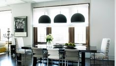 Sleek modern kitchen with three black dome pendant lights hung over a black dining room table surrounded by upholstered chairs with higher b...