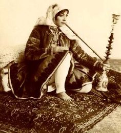 A woman smoking hookah, Iran, ca. 1900.